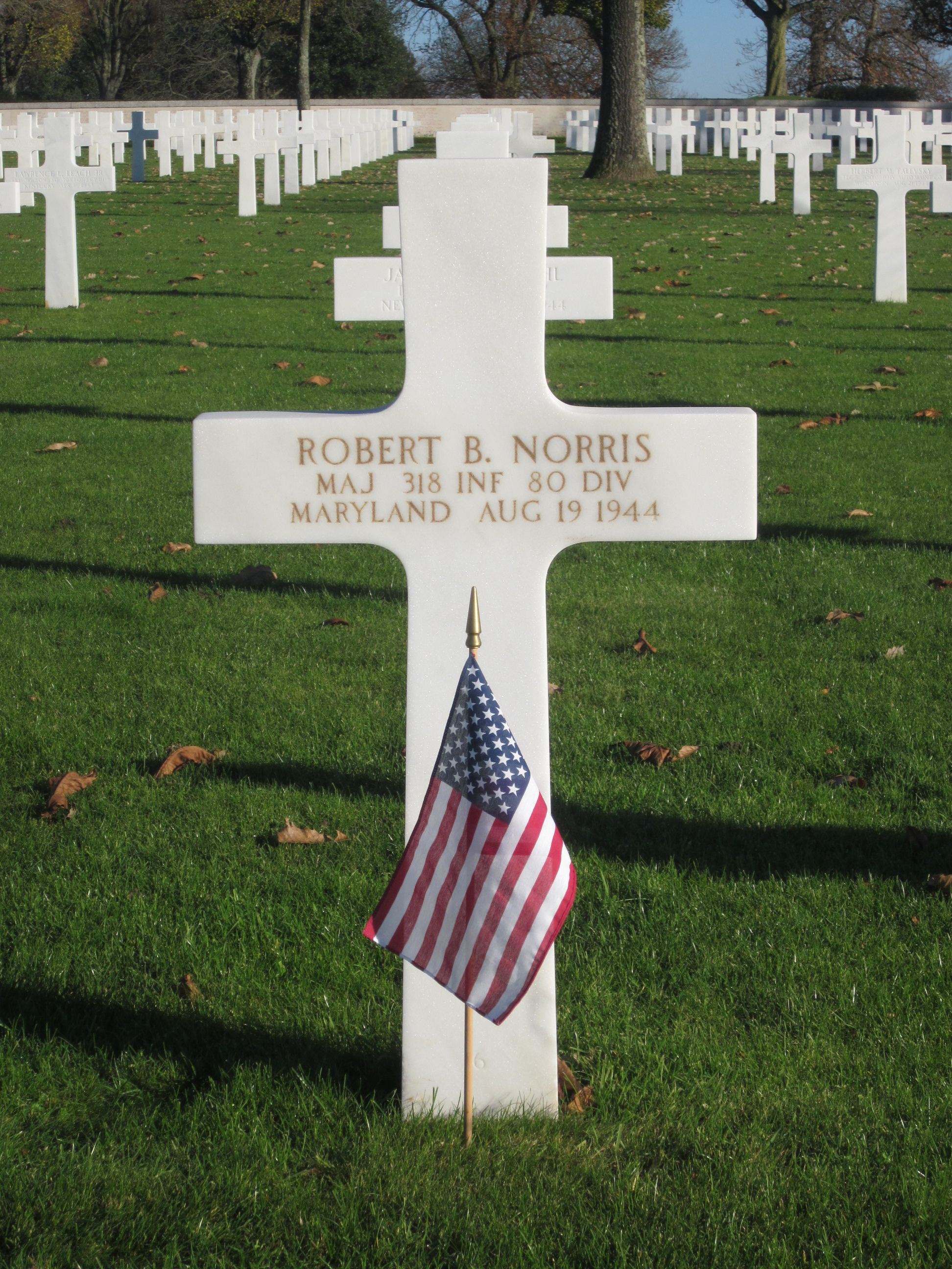 Photo of white cross marker with words Robert B. Norris Maj 318 Inf 80 Div Maryland Aug 19 1944. A US flag is planted in front of the marker.